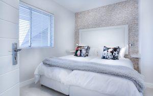 חדר שינה מסודר עם כריות על המיטה